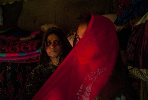 """LAHORE, PAKISTAN- NOVEMBER 2009 A few days ahead of her wedding, fourteen year old Afghan refugee Zeenat Gul is helped by her mother as she tries on her hand made red beaded wedding dress at their one room home in the slums of Sagiam Pull. One of ten siblings, Zeenat was born at the refugee camp of Kohart in Pakistan's North West Frontier Province after her family fled fighting in Kunduz. Relocating to the suburbs of Lahore, they now live along with thousands of other Afghanis in  a camp beside the city's garbage dump where the marginalised community survive by recycling other peoples' rubbish. Zeenat Gul has yet to meet her fiance but has been busy making her in-laws to be gifts of beaded combs, mirrors and jewelry. Now liberated from her work in the dump, her mother Barangul has been advising her teenage daughter about marriage. The sensitive topic of sex will not be raised until the wedding night, """"When a girl marries, then she will become a woman""""."""